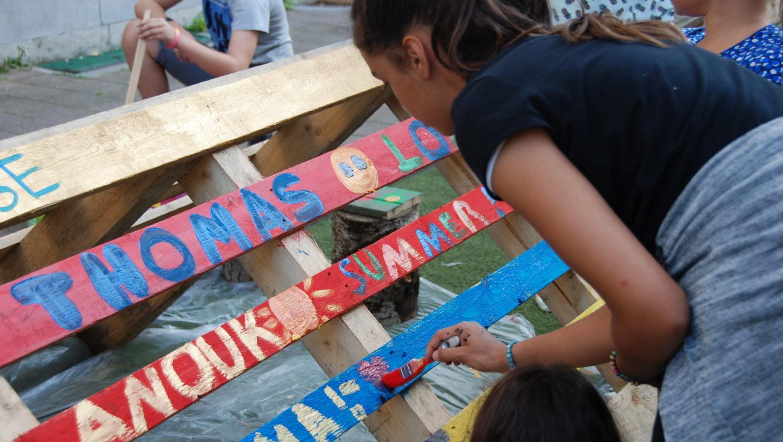 kinderen schilderen een bank op straat