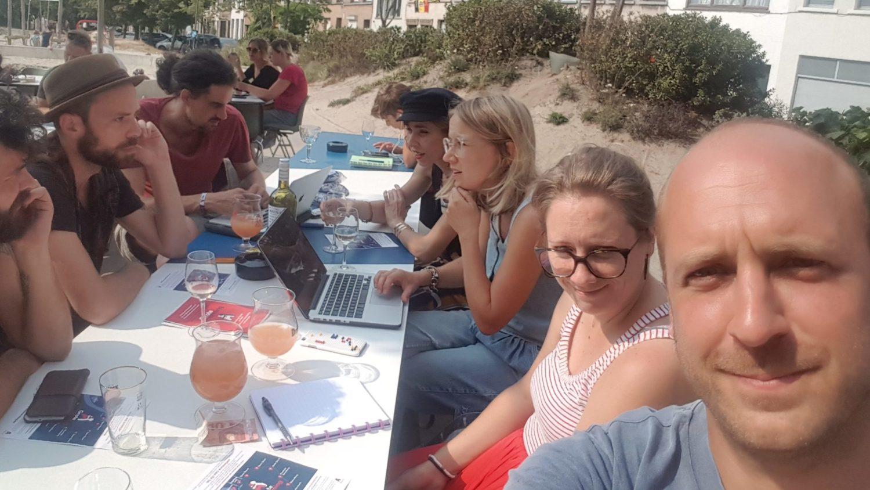Groep mensen aan tafel op straat vergaderend